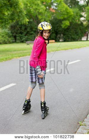 Little Girl Rolller Skating In A Park