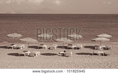 Greece. Kos Island. Kefalos. Chairs And Umbrellas On The Beach. In Sepia Toned. Retro Style