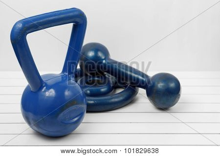 Weight, Dumbell And Kettlebell On A White Wooden Floor