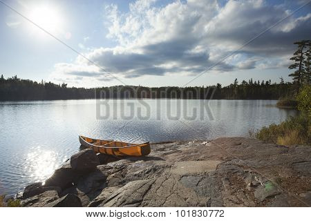 Orange Canoe On Rocky Shore Of Boundary Waters Lake Near Sundown