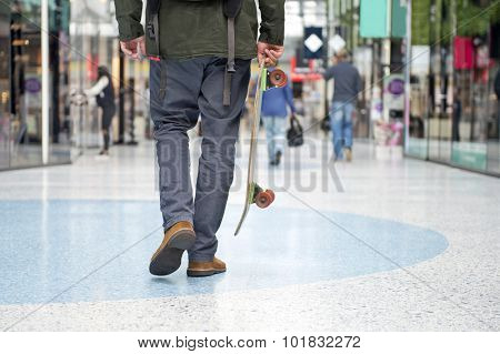 Guy from the waist down with a skateboard, walking casually through a modern shopping mall