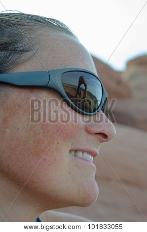 Delicate arch reflects in the sunglasses of a happy hiker overlooking the stunning geological view