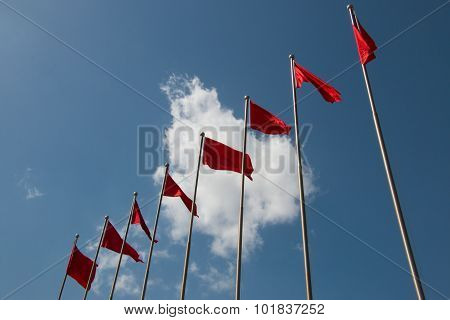 Line Of Red Flags In Front Of Cloudy Blue Sky