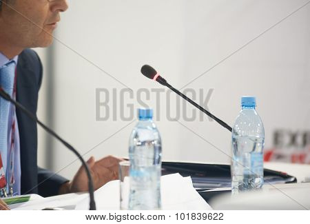 Speaker at business conference and presentation. Focus to microphone. No recognizable faces