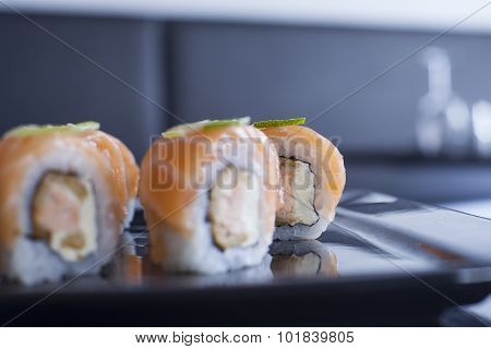 Sushi Roll With Cream Cheese And Fried Salmon. Topped With Raw Salmon And Lime.