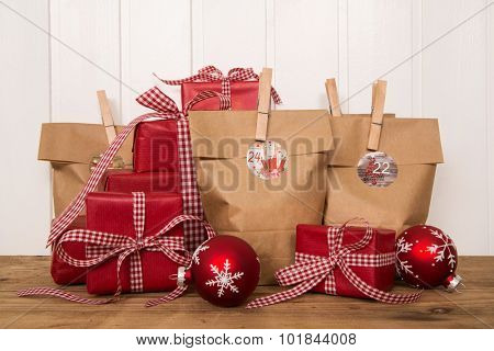 Handmade christmas presents wrapped in paper bags and presents with red white checked ribbon on wooden white background.