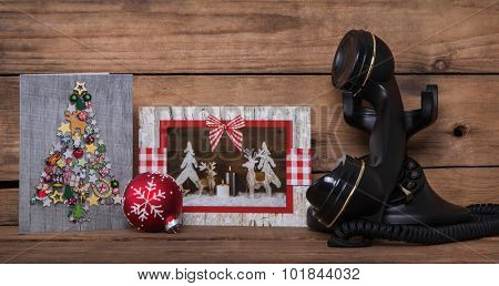 Writing or calling friends on christmas time. Wooden background with greeting cards and an old nostalgic phone.