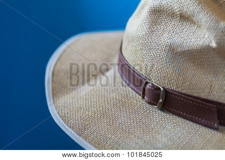 Blurred Blue Image Of A Cream Hat With White Fringe And Brown Strap
