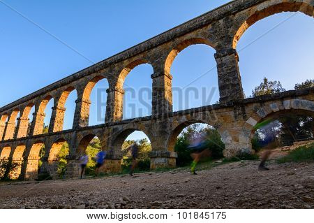 Beautiful View  Of Roman Aqueduct Pont Del Diable In Tarragona At Sunset With People Jogging In Fron