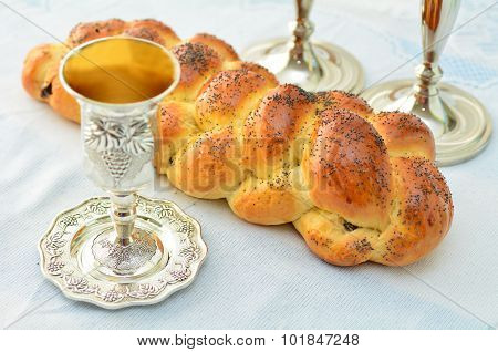 Shabbat eve table with uncovered challah bread Sabbath candles and Kiddush wine cup.