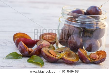 Heap Of Plums In Glass Jar On Wooden Table In Garden