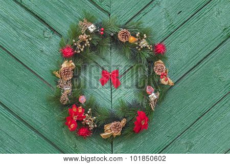 Outdoor hanging Christmas adorn wreath at old green wooden door background