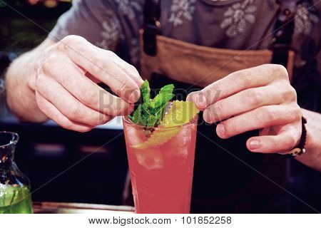 Bartender is adding mint to the cocktail at bar counter, toned image