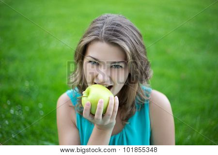 Portrait Of Young Beautiful Woman Biting Apple In Summer Park
