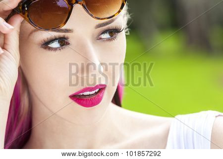 Outdoor portrait of a beautiful young woman or girl with brown eyes, blond and magenta pink hair wearing sunglasses