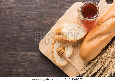 Rustic Bread Or Baguette With Honey On The Wooden Background