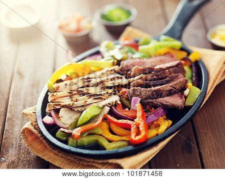 mexican food - skillet fajitas with steak and chicken on rustic wooden table