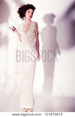 Beautiful Woman Model Posing In Elegant Pearl Dress In The Studio