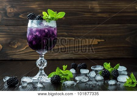 Tasty blackberry cocktail in wine glass with mint and ice on dark wooden table. Summer berry lemonad