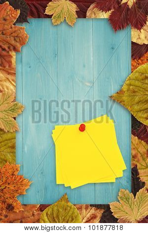Sticky note with red pushpin against autumn leaves on wood