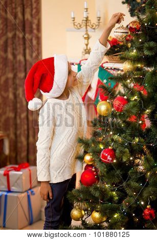 Little Girl In Santa's Hat Putting Ball On Top Of Christmas Tree