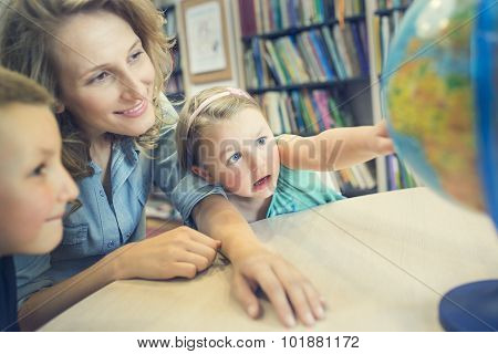 Education. Side View Of Little Kids Pointing At Globe In Classroom