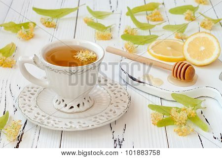 Cup of herbal tea with linden flowers lemon and honey on a old wooden background