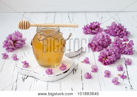 Robinia honey with acacia blossoms on old wooden table