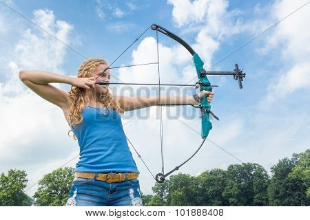 Blonde Caucasian Girl Shooting With Arrow And Compound Bow