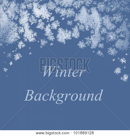 Winter background with frosty ice crystals and copy space on solid blue color