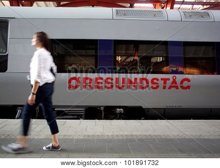 MALMO, SWEDEN - FRIDAY, AUGUST 21, 2015: A pedestrian walks past a Oresundstag train at the main station in Malmo, Sweden. The train links Malmo with nearby Copenhagen, Denmark.