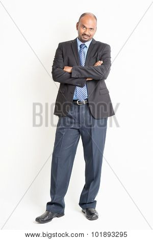Portrait of full body confident mature Indian business man arms crossed, standing on plain background.