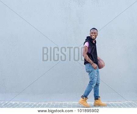 Happy Young Man Walking On Sidewalk With Basketball