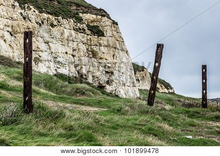 Rusting fence posts by a cliff