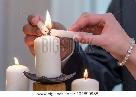 Couple lighting up candle as a symbol of love