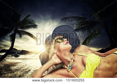 Beautiful woman in sensual swimsuit at the golden sunshine glow of sunset