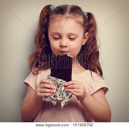 Happy Kid Girl Eating Dark Chocolate With Pleasure And Closed Eyes. Vintage Portrait