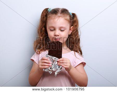 Happy Kid Girl Eating Dark Chocolate With Pleasure And Closed Eyes