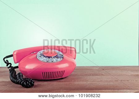 Retro telephone set on wooden table on turquoise background