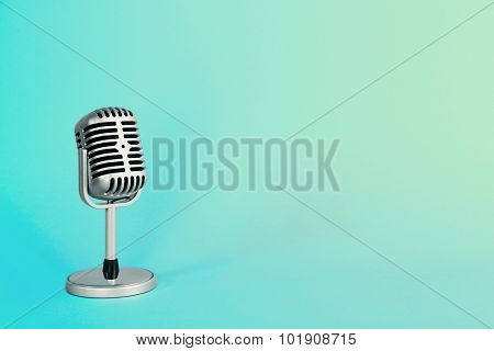 Old metal microphone on turquoise background