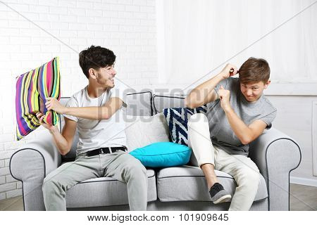Two brothers fighting with pillows on sofa at home