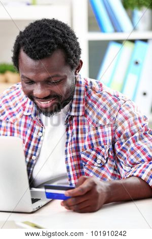 African American man with laptop and credit card at workplace
