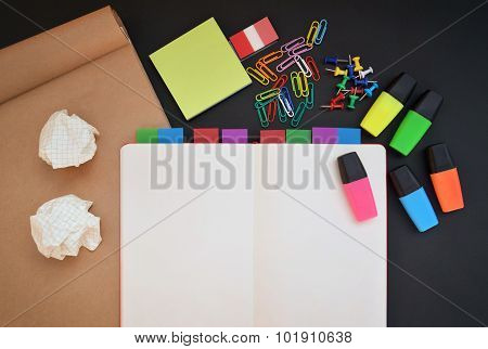 Creative workspace with open notebook, craft, colorful highlighters, clips and pins on black desk