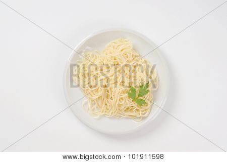 plate of cooked noodles on white background