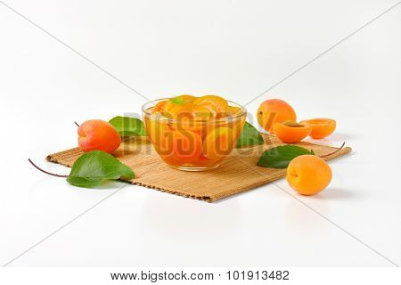 apricot compote in the glass bowl with straw linen, accompanied by green leaves