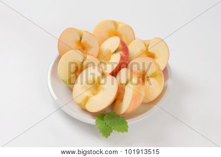 plate of halved and seedless apples on white background