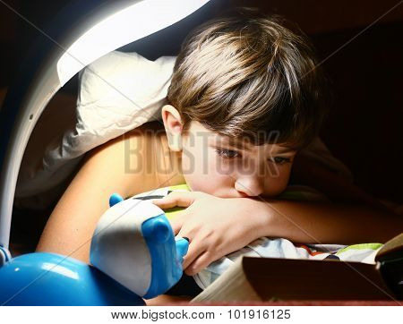 Preteen Handsome Boy Read Book With Lamp Before Sleep