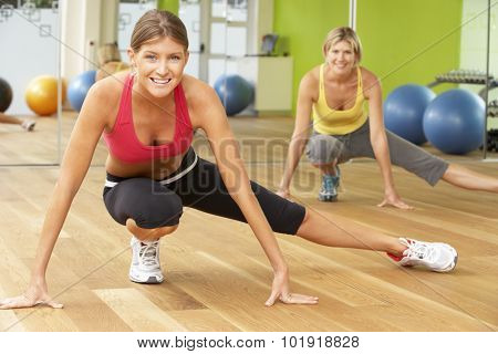 Two Women Taking Part In Gym Fitness Class