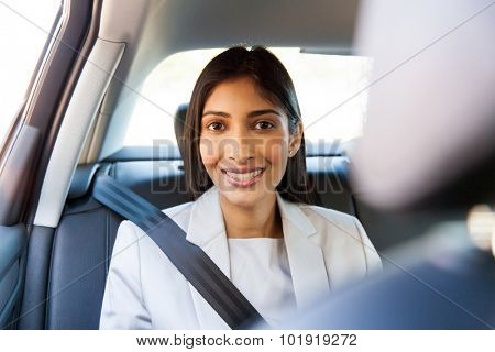 portrait of happy indian businesswoman sitting in car backseat
