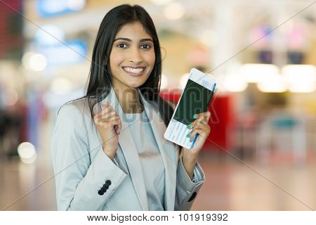 excited indian woman holding passport and boarding pass at airport